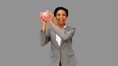 Businesswoman listening to a full piggy bank on grey screen — Stock Video