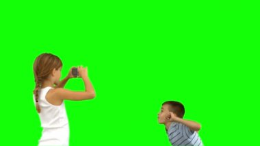 Sister taking pictures of her brother jumping on green screen — Stock Video