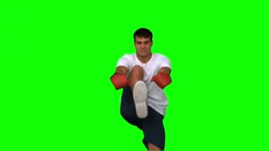 Handsome boxer performing a high kick on green screen — Stock Video