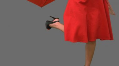 Woman in high heels holding a broken umbrella on grey screen — Stock Video