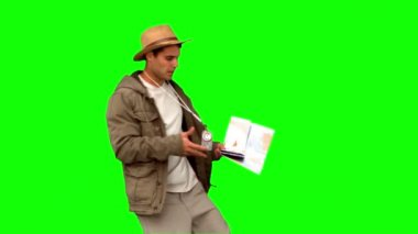 Man with a map and a compass orienteering on green screen — Stock Video
