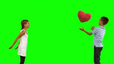 Siblings playing with a heart shaped cushion on green screen — Stock Video