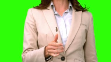 Pretty businesswoman throwing a coin on green screen — Stock Video