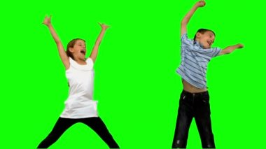 Brother and sister jumping together on green screen — Stock Video