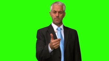 Elegant businessman throwing a coin in the air on green screen — Stock Video