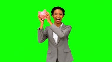 Businesswoman listening to a full piggy bank on green screen — Stock Video