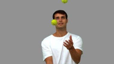 Man dribbling with tennis balls on grey screen — Stock Video