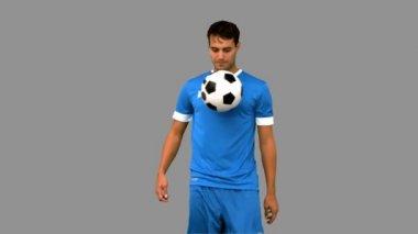Man jonglering en fotboll med sitt knä på grå skärm — Stockvideo