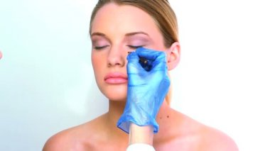 Beautiful blond woman preparing for surgery while surgeon drawing lines on her face