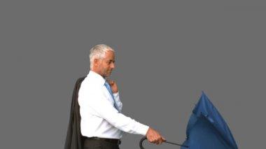 Businessman going under his umbrella on grey screen — Stock Video