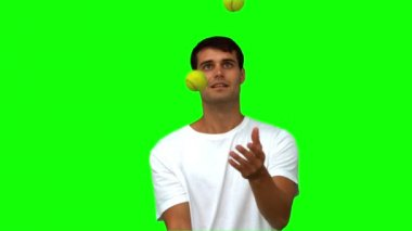Man dribbling with tennis balls on green screen — Stock Video