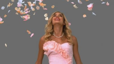 Woman in ballgown standing under petals falling on grey screen — Stock Video