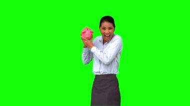 Businesswoman shaking a full piggy bank on green screen — Stock Video