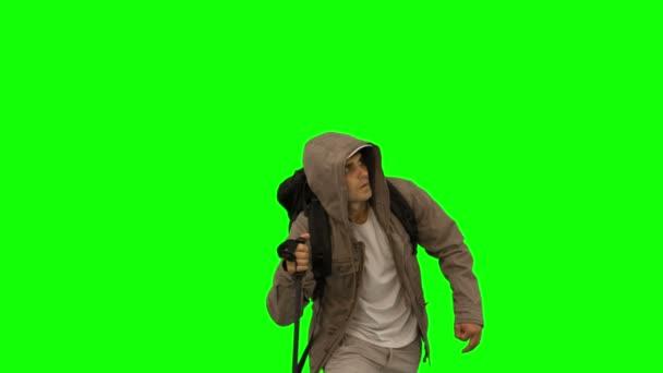 Hombre atractivo con una capa de trekking en pantalla verde — Vídeo de stock