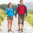 Hikers with backpacks holding hands and walking — Stock Photo #31459401
