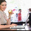 Happy businesswoman holding wine glass using laptop and looking at camera — Stock Photo