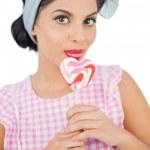 Pretty black hair model licking a heart shaped lollipop — Stock Photo