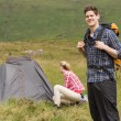 Smiling man carrying backpack while girlfriend is pitching tent — Stock Photo
