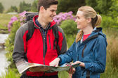 Happy couple reading map on a hike — Stock Photo