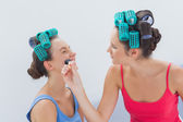Friends in hair rollers having fun with makeup — Stock Photo
