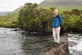 Blonde femme debout sur un rocher dans un flux — Photo
