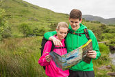 Athletic couple in hooded jumpers on a hike reading map — Foto Stock