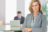 Unsmiling businesswoman looking at camera crossed arms with a businessman working on background — Stock Photo