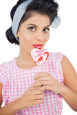 Pretty black hair model licking a heart shaped lollipop — Stock Photo