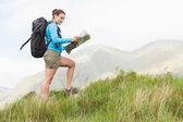 Aantrekkelijke wandelaar met rugzak lopen bergopwaarts lezen van een kaart — Stockfoto