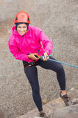 Happy girl abseiling down rock face — Stock Photo