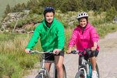 Un couple heureux sur un vélo rouler habilement pulls à capuchon — Photo