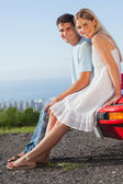 Happy couple sitting on their cabriolet car hood — Stock Photo
