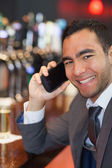 Happy businessman on the phone having a drink — Stock Photo