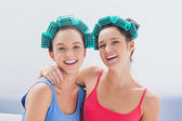 Girls in hair rollers and pajamas smiling at camera — Stock Photo