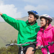 Smiling couple on a bike ride wearing hooded jumpers with man pointing — Stock Photo #31460001