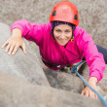 Happy girl climbing up rock face — Stock Photo