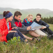 Friends sitting on grass and looking at map on camping trip — Stock Photo