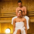 Mgiving his girlfriend neck massage in sauna — Stock Photo #31460569