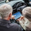Mature partners working together on tablet in classy car — Stock Photo