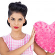 Unsmiling black hair model holding a pink heart shaped pillow — Stock Photo