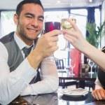 Улыбаясь деловых партнеров звон бокалов, глядя на камеру — Стоковое фото
