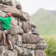 Focused man climbing a large rock face — Stock Photo