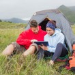 Couple on camping trip using a digital tablet — Stok fotoğraf