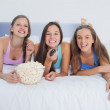 Friends eating popcorn and laughing — Stock Photo