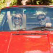 Loving couple having fun in their red cabriolet — Stock Photo