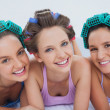 Stock Photo: Friends in hair rollers and pajamas lying in bed