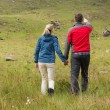 Couple holding hands on walk with man pointing — Stock Photo