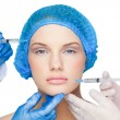 Surgeons making injection on calm blonde wearing blue surgical cap — Stock Photo