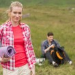 Happy woman carrying camping mat — Stockfoto