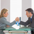 Two businesspeople having a showdown sitting around a table — Stock Photo